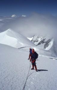 Vi har ladt skyerne bag - og nedenfor - os og går nu under en skyfri himmel mod toppen af Mont Blanc